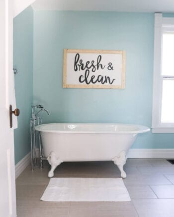 Fixer Upper Bathroom Before and Afters... fixer upper style bathroom makeover with clawfoot tub, watery paint color and sliding bar door. Clean, fresh, and airy bathroom!