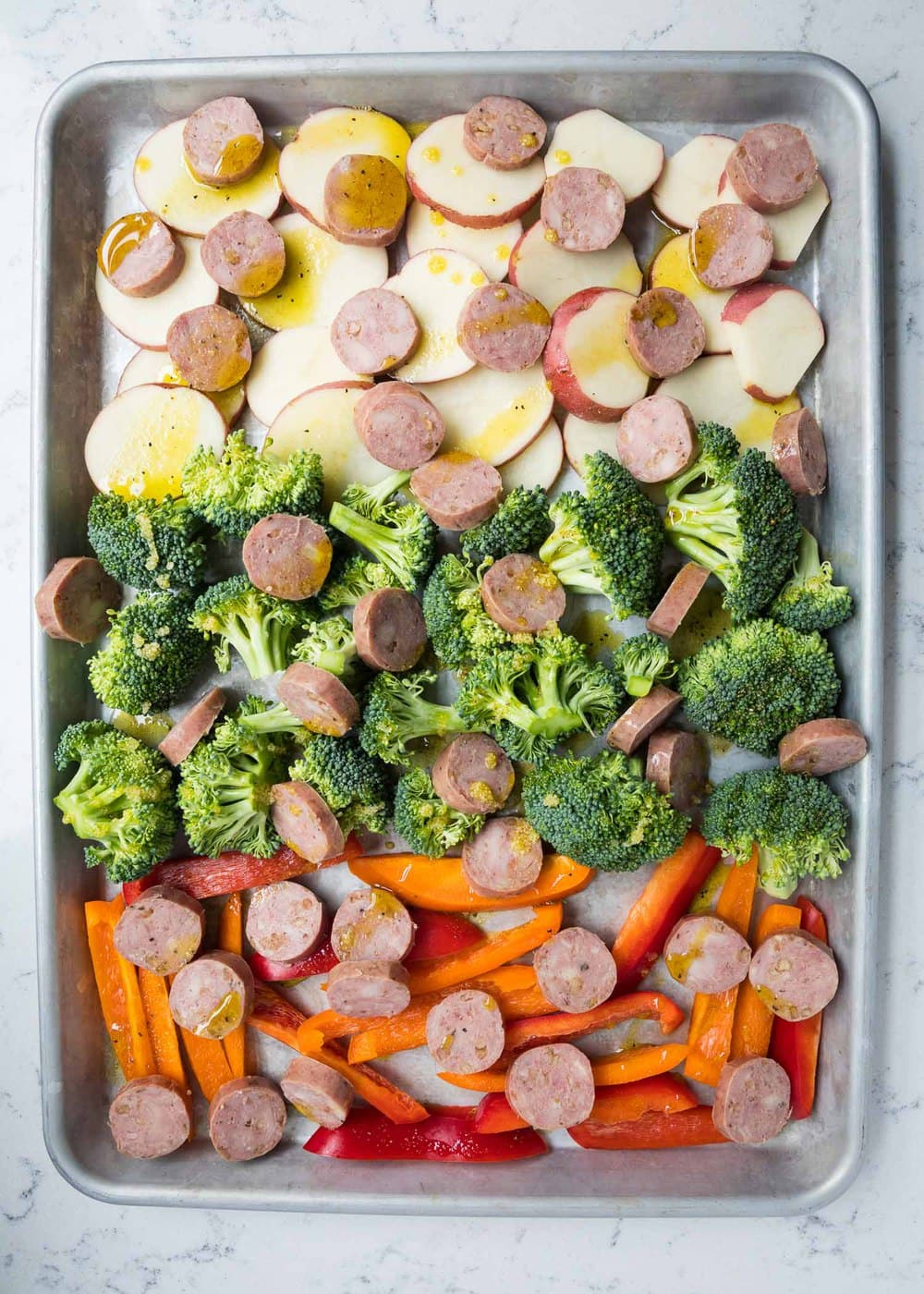 sausage and veggies drizzled with olive oil on baking sheet