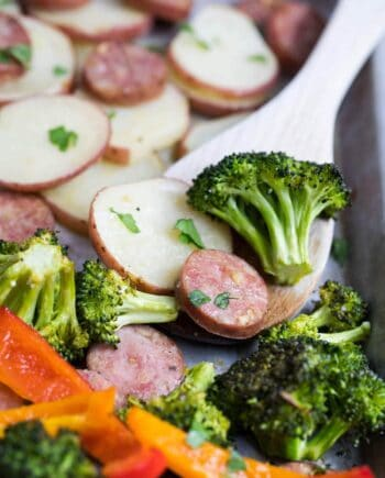 roasted sausage and veggies on a wooden spoon