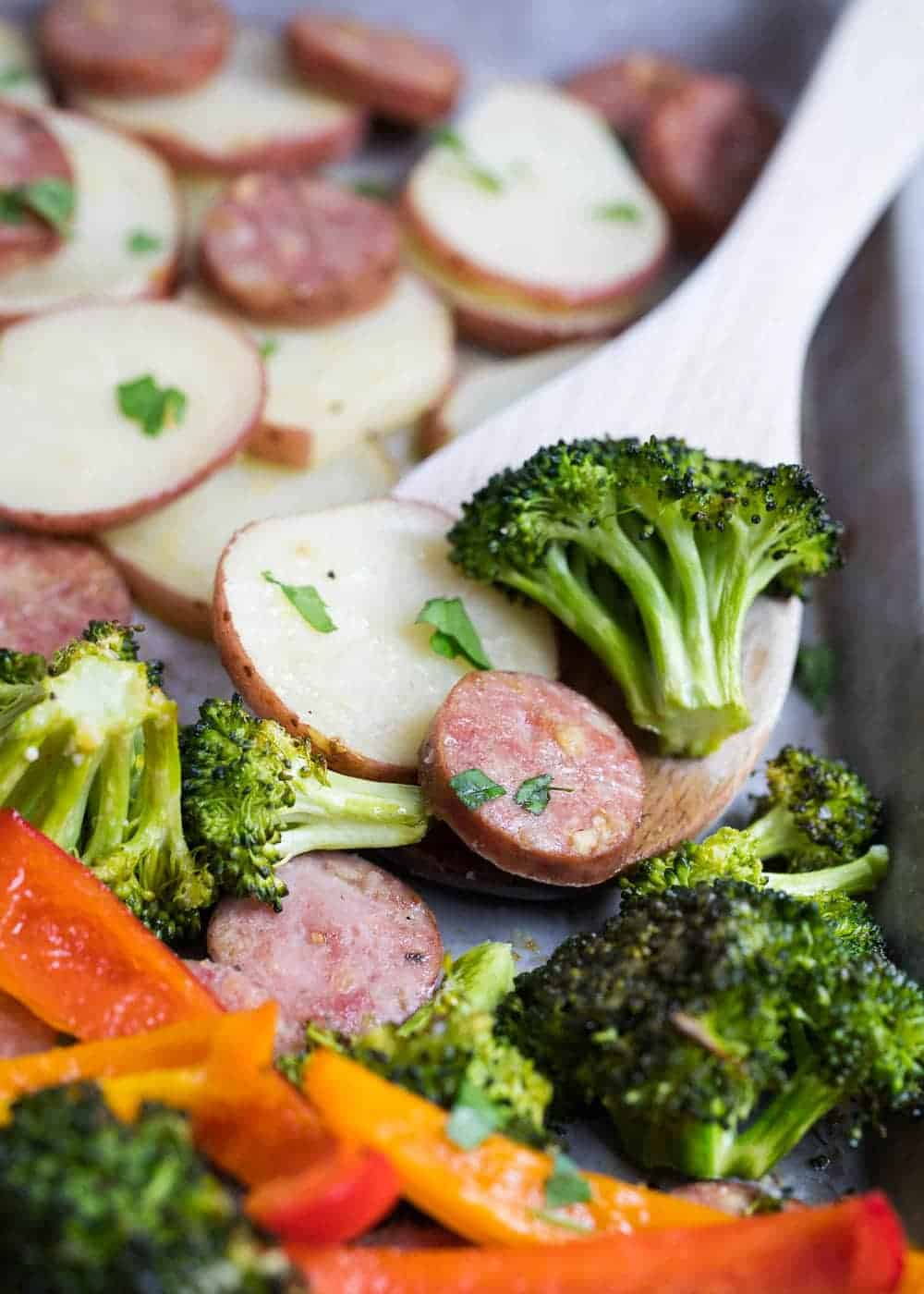 sheet pan sausage and veggies with a wooden spoon