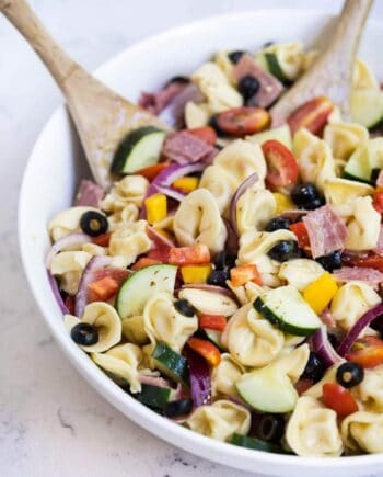 italian tortellini pasta salad in a bowl with a wooden spoon