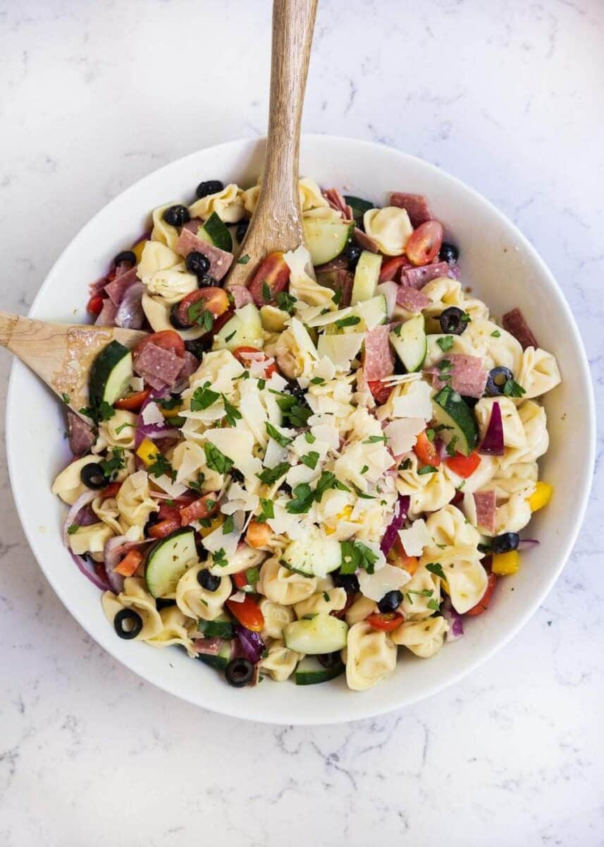 bowl of tortellini salad with wooden spoon