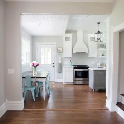 a kitchen with a table and hardwood floors
