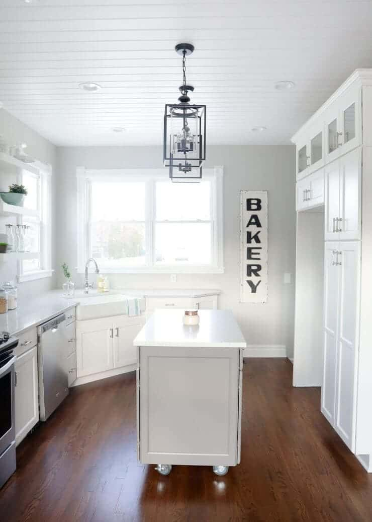 Modern farmhouse kitchen makeover with amazing before and after photos -white and grey cabinets with wood floors and planked ceilings.