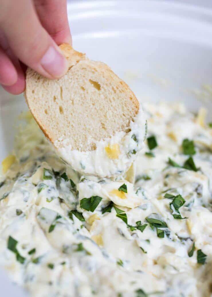 The BEST cheesy hot spinach artichoke dip -a delicious appetizer that is perfect for any party and made extra EASY in the slow cooker!