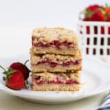 stack of strawberry crumb bars on a white plate