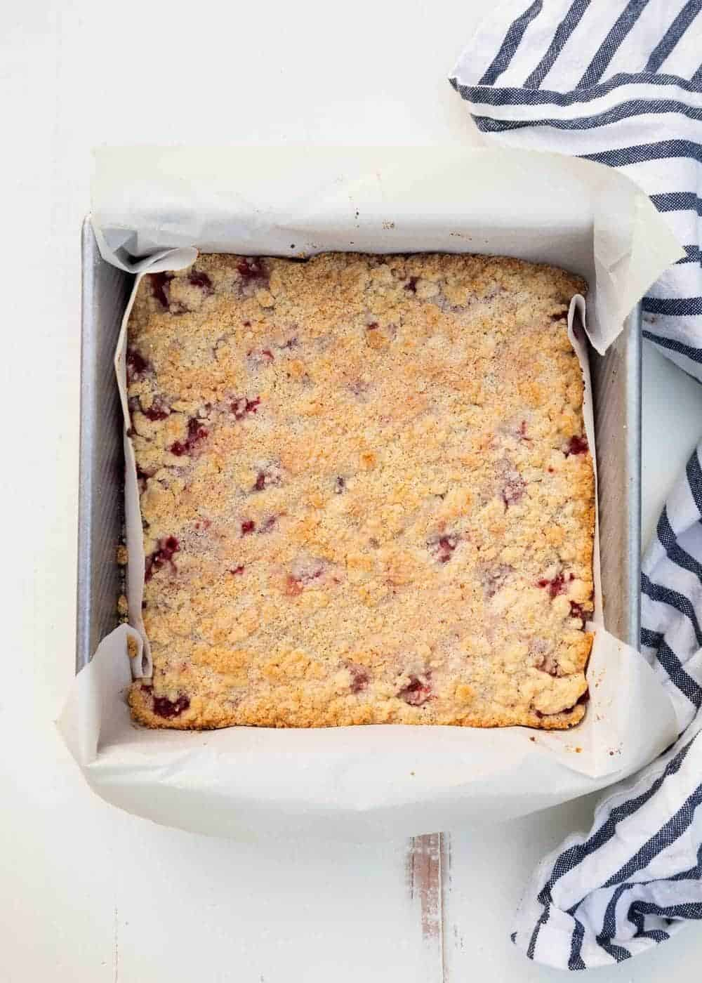 strawberry crumble bars in a parchment lined pan