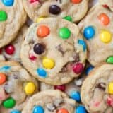 A close up of a pile of M&M cookies