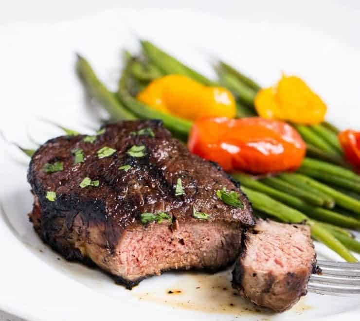 grilled steak with grilled green beans and tomatoes on a white plate