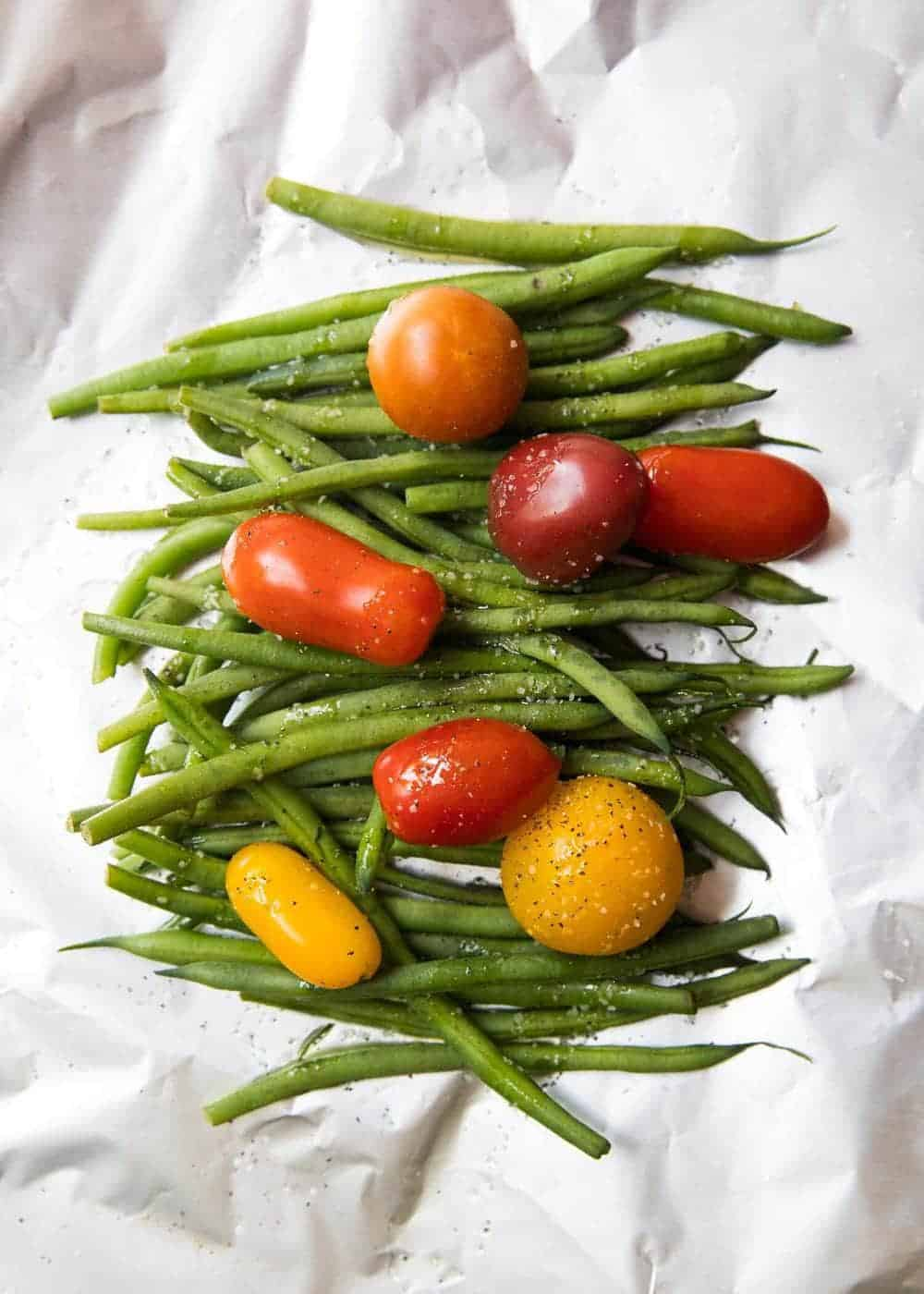 seasoned green beans and tomatoes on a piece of foil