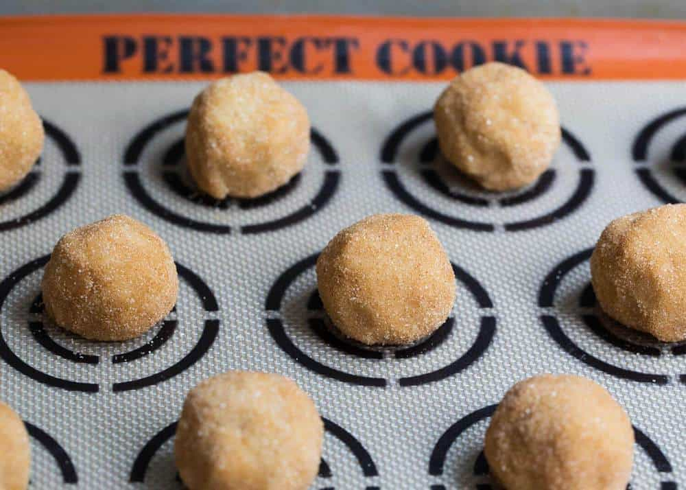 snickerdoodle cookie dough balls on a silicone cookie mat