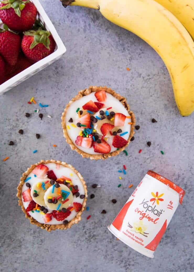 This simple recipe for yogurt sundaes is made with vanilla yogurt in a waffle cup with fresh fruit, chocolate and sprinkles on top. Easy and delicious!