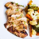 sliced grilled chicken on a plate with veggies