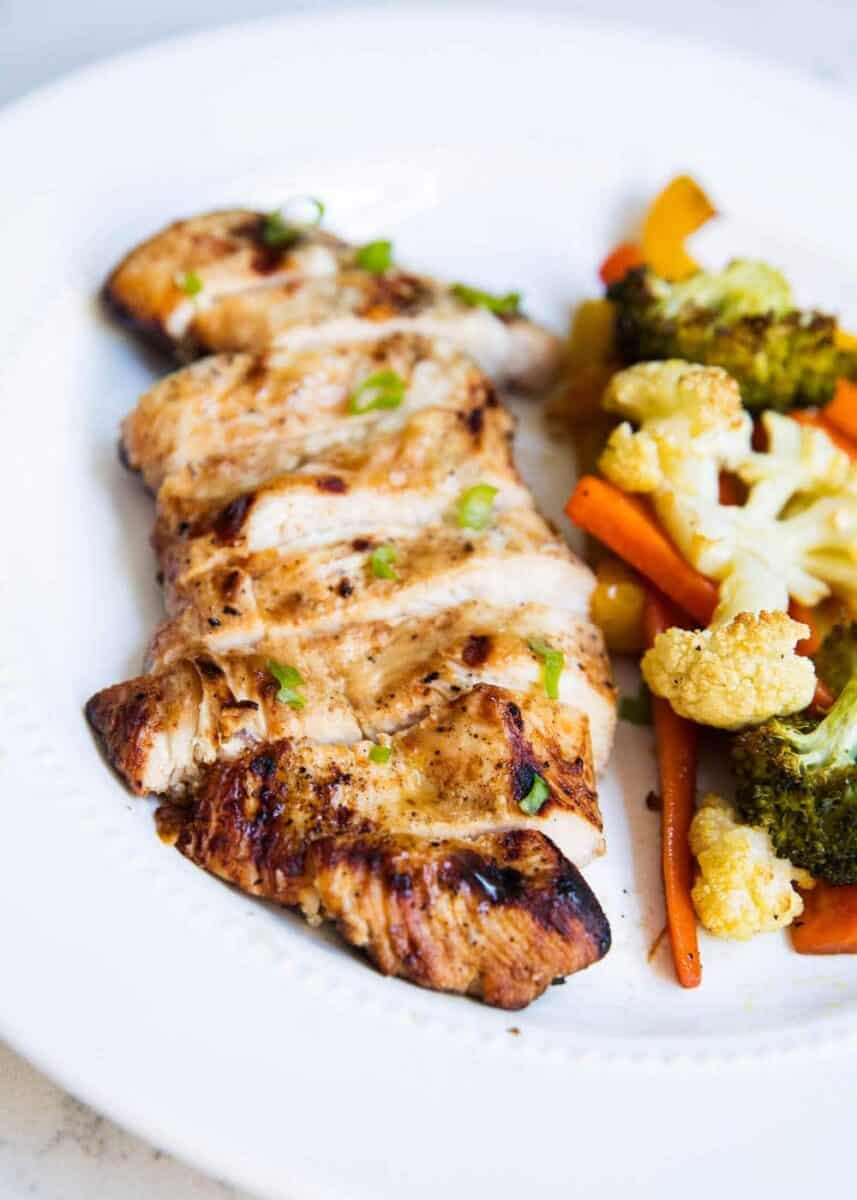 sliced chicken on white plate with vegetables