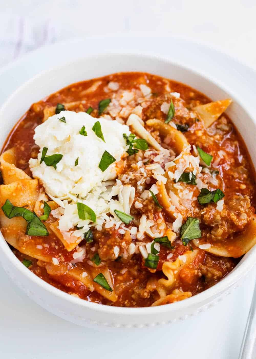 bowl of lasagna soup topped with ricotta and chopped basil