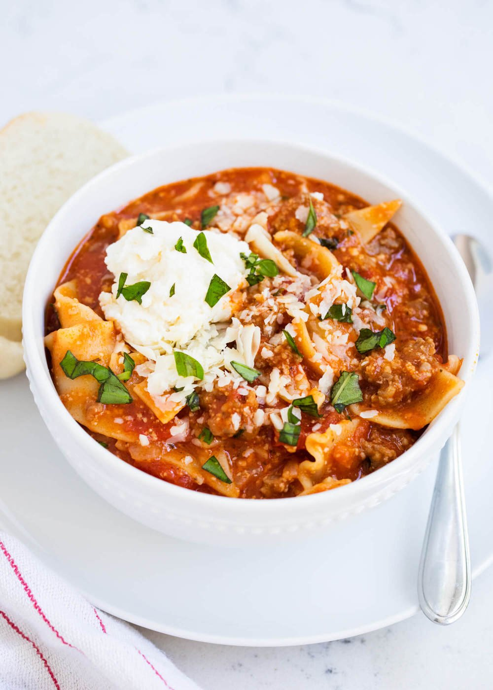 bowl of lasagna soup topped with ricotta and fresh basil