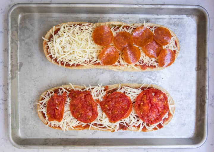 pizza bread on baking sheet with toppings