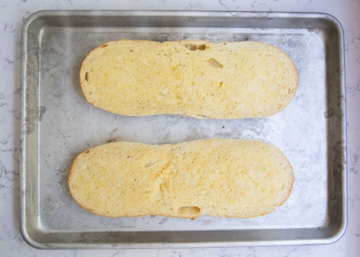 garlic french bread loafs on baking sheet