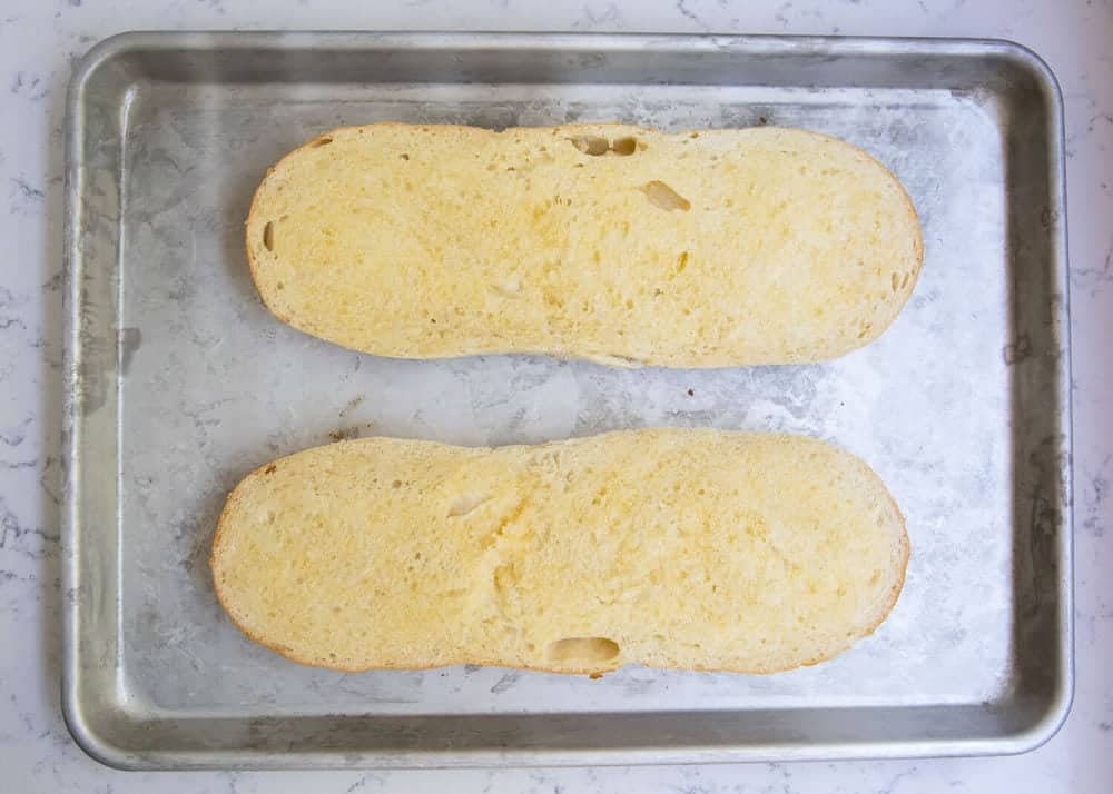 garlic bread loafs on baking sheet