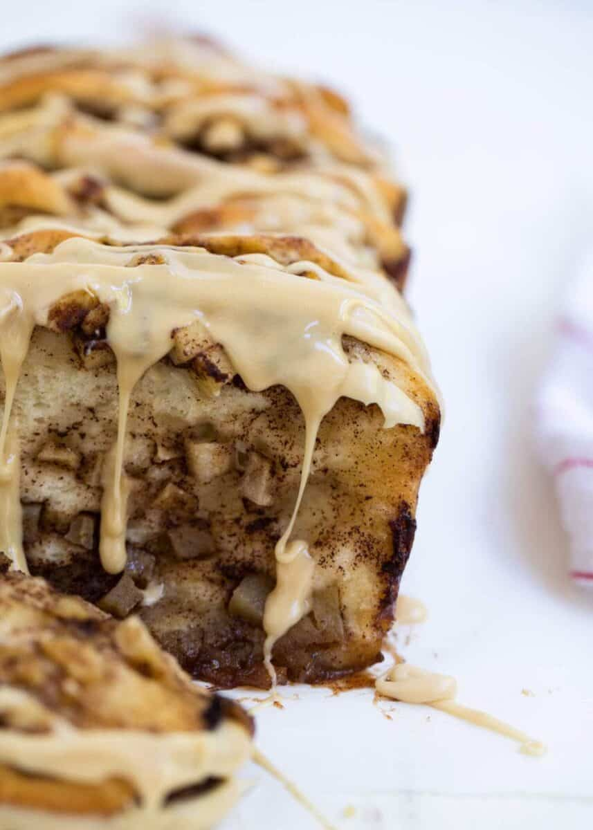 loaf of cinnamon apple pull apart bread with caramel icing dripping over sides