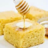 drizzling honey on top of a piece of sweet cornbread