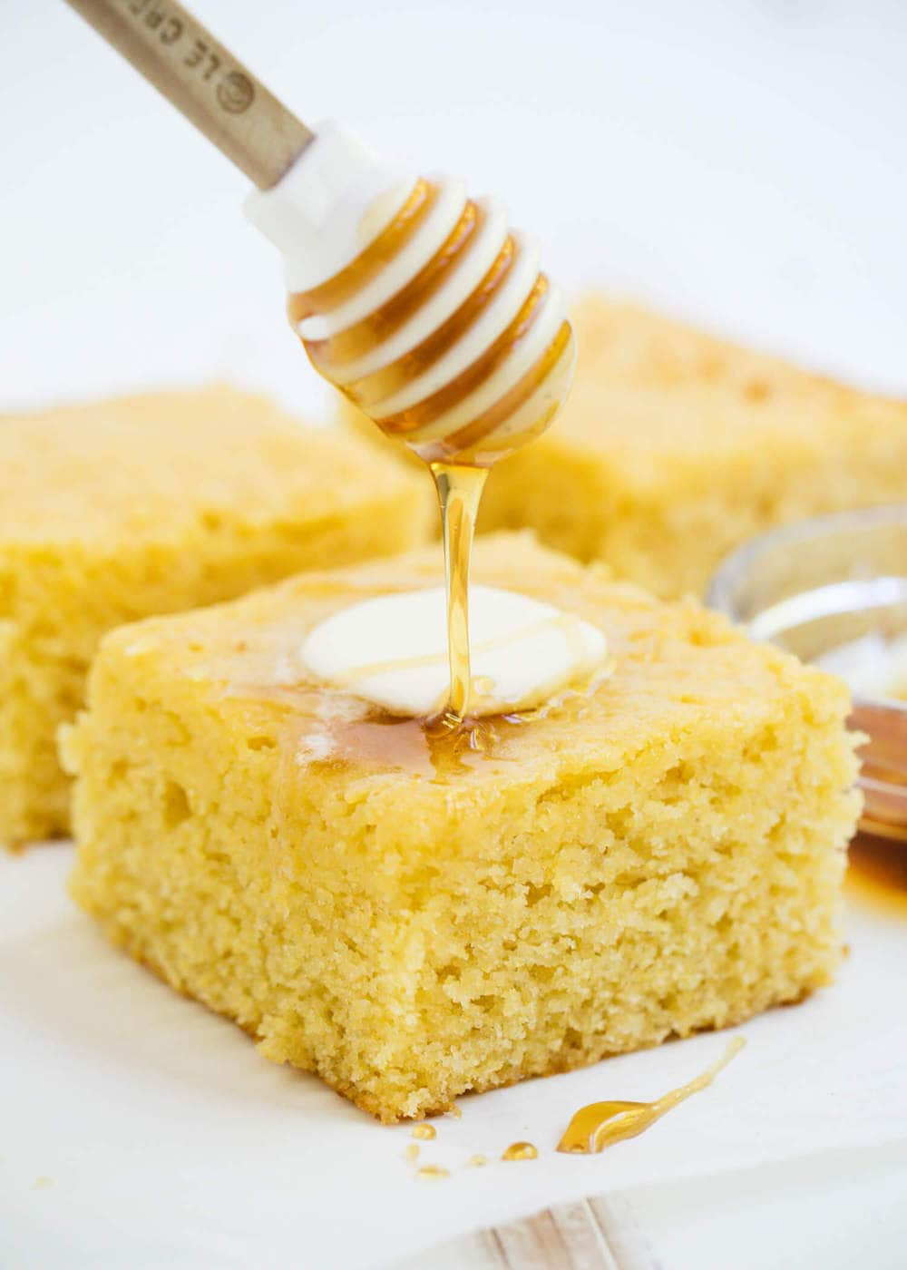 honey wand dripping honey onto a piece of homemade cornbread