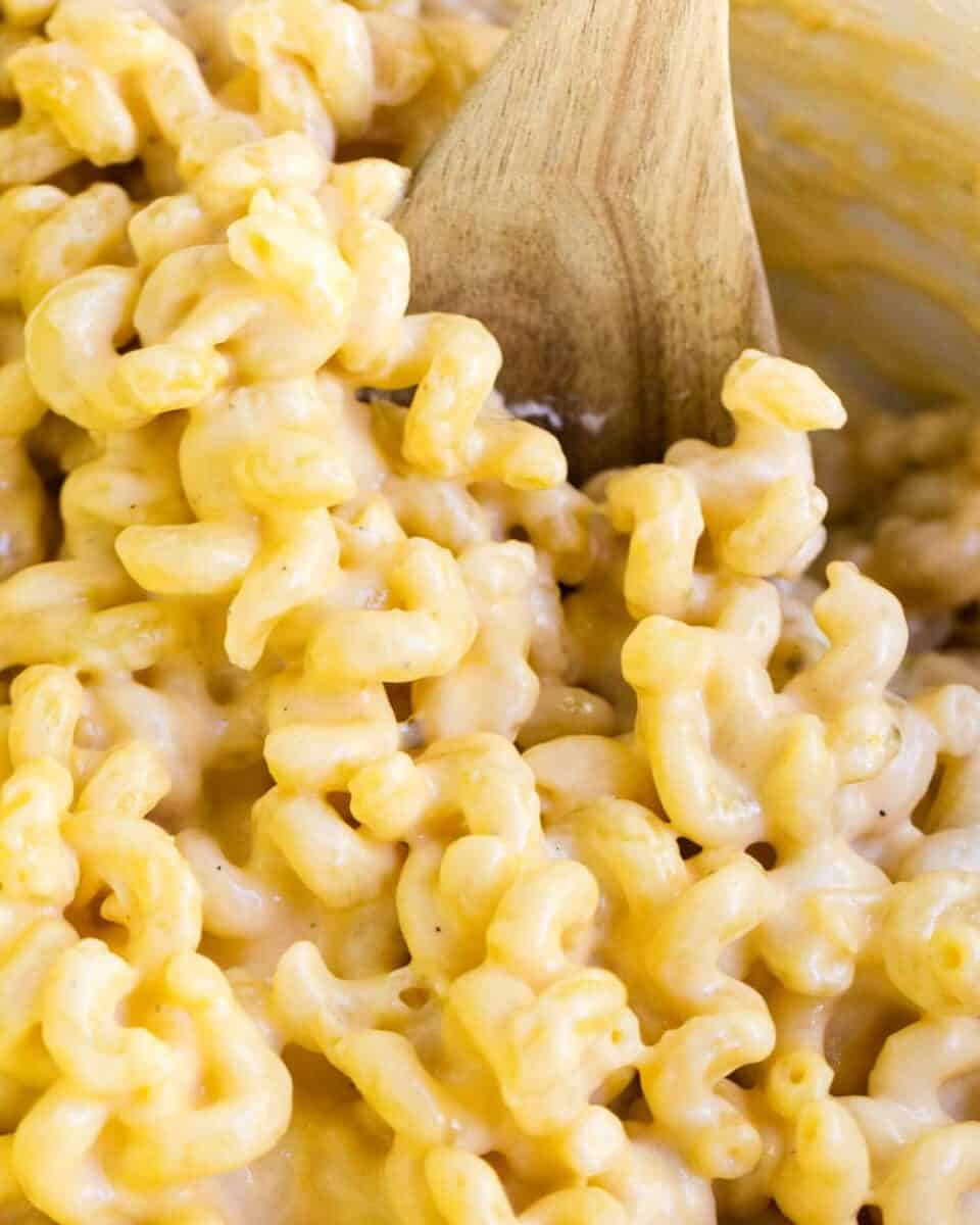 mac n cheese with a wooden spoon
