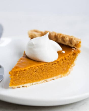 A piece of pumpkin pie on a plate with a dollop of whipped cream on top