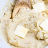 wooden spoon in slow cooker mashed potatoes with butter slices on top