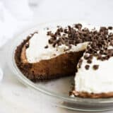 chocolate silk pie in a pie pan with a slice taken out