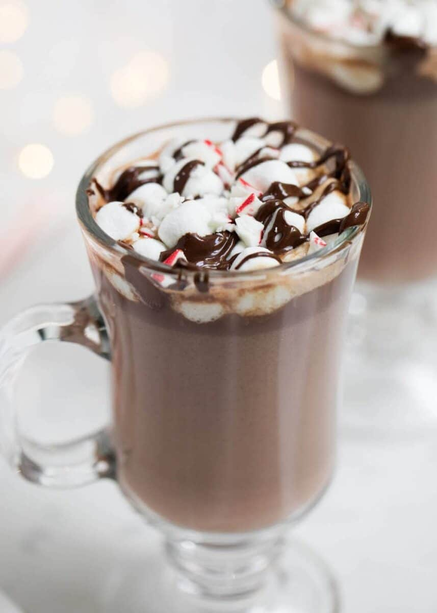 hot chocolate in a glass mug topped with mini marshmallows, hot fudge and crushed peppermint