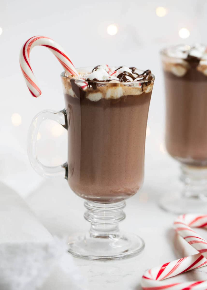 homemade hot chocolate in glass mug with candy cane