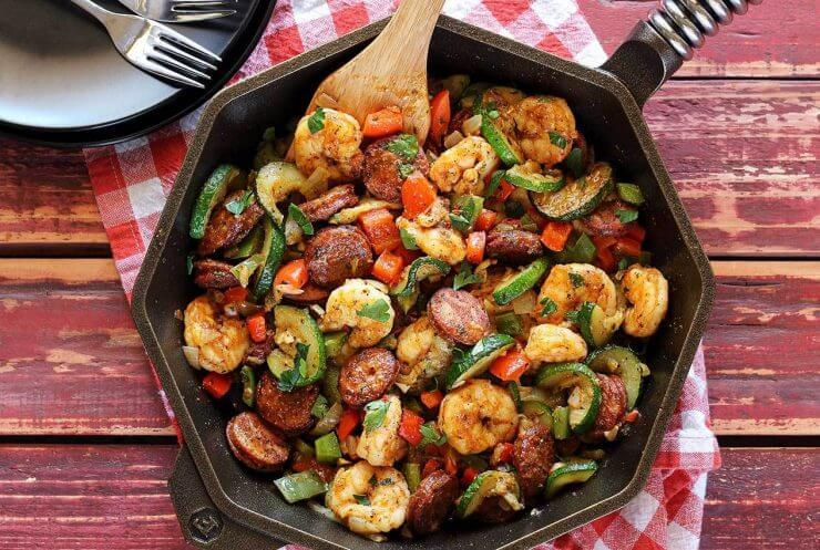 shrimp and sausage in a cast iron skillet with wooden spoon