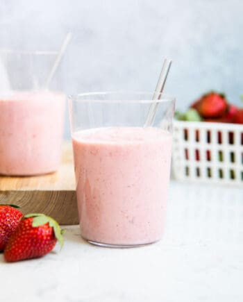 strawberry banana smoothie in a glass with a straw