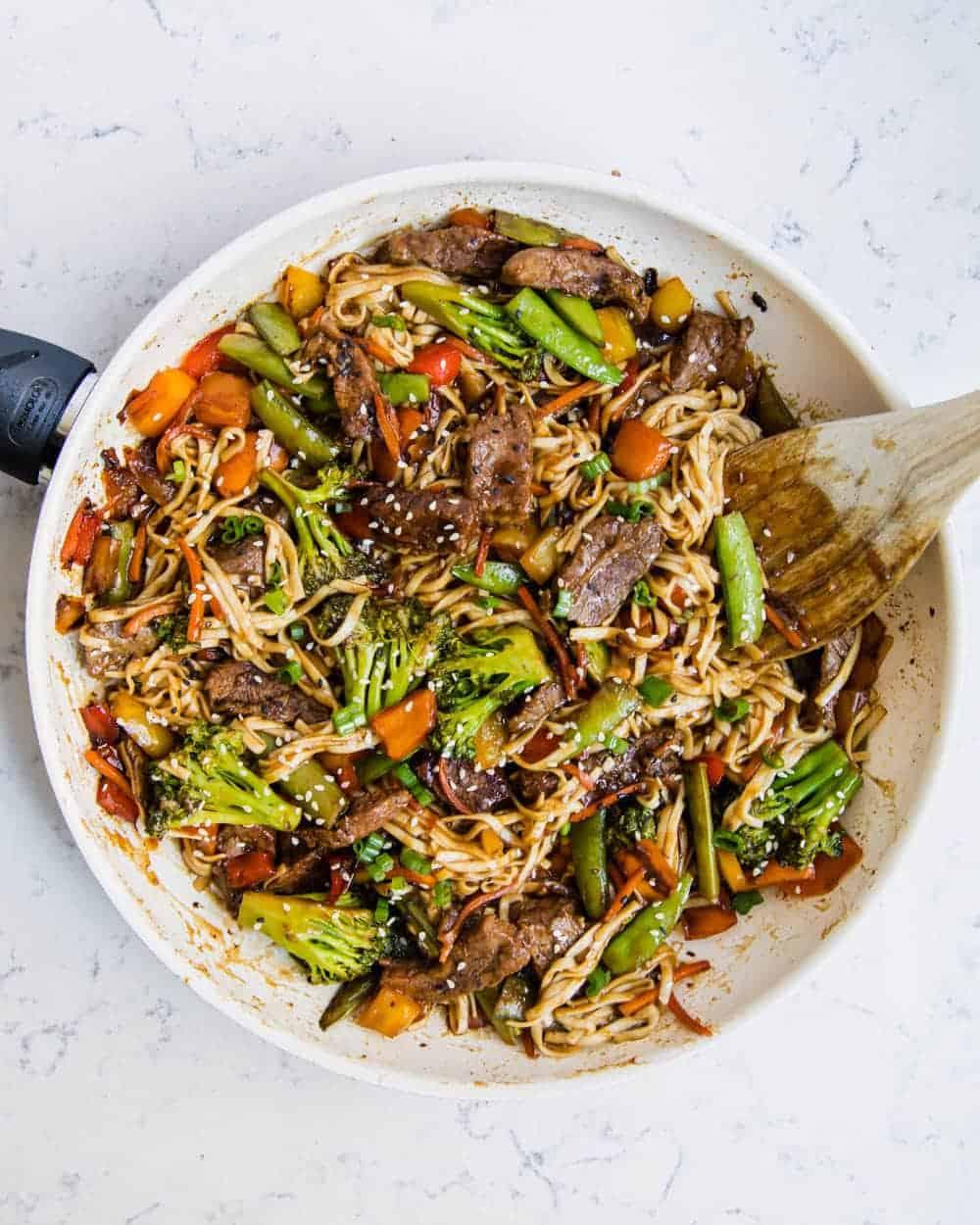 beef ramen recipe in pan with wooden spoon