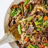 beef ramen in a pan with a wooden spoon