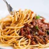 A close up spaghetti with bolognese sauce on a fork