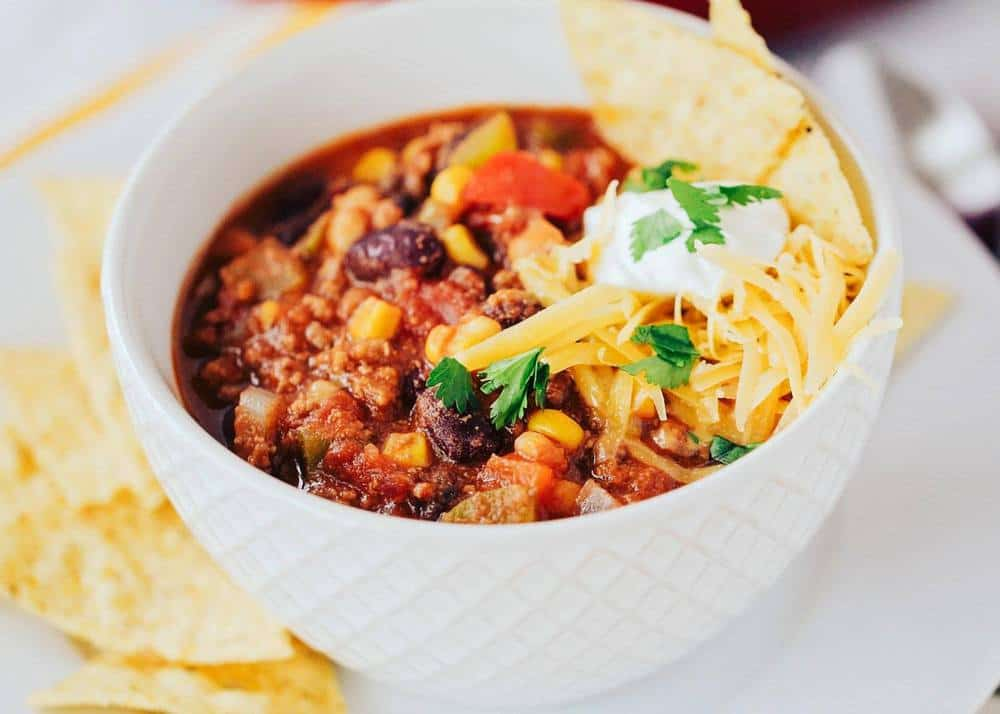bowl of taco soup topped with cheese, sour cream, cilantro and tortilla chips
