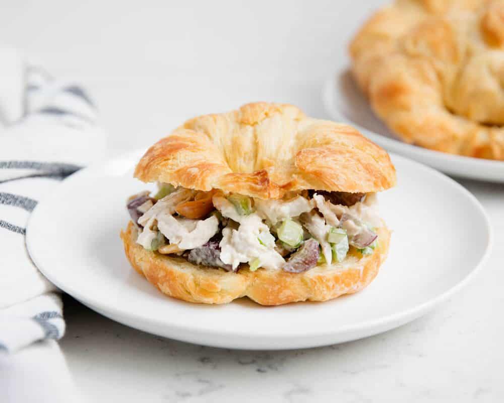chicken salad croissant sandwich on white plate