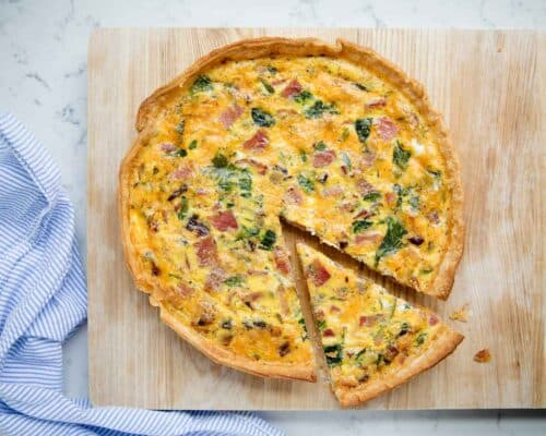 ham and cheese quiche on a cutting board with a slice cut out