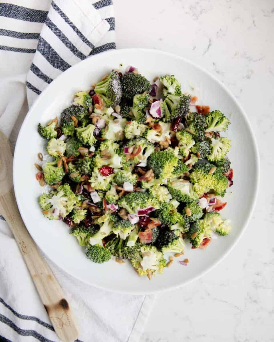 overhead shot of broccoli bacon salad in white bowl
