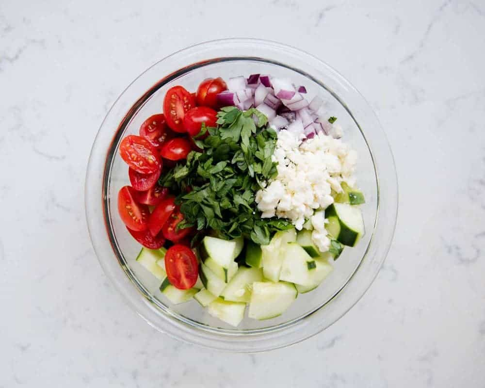 chopped ingredients for cucumber tomato salad in a glass bowl