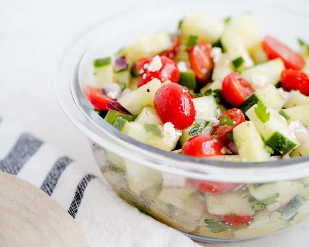 cucumber tomato salad in a glass bowl