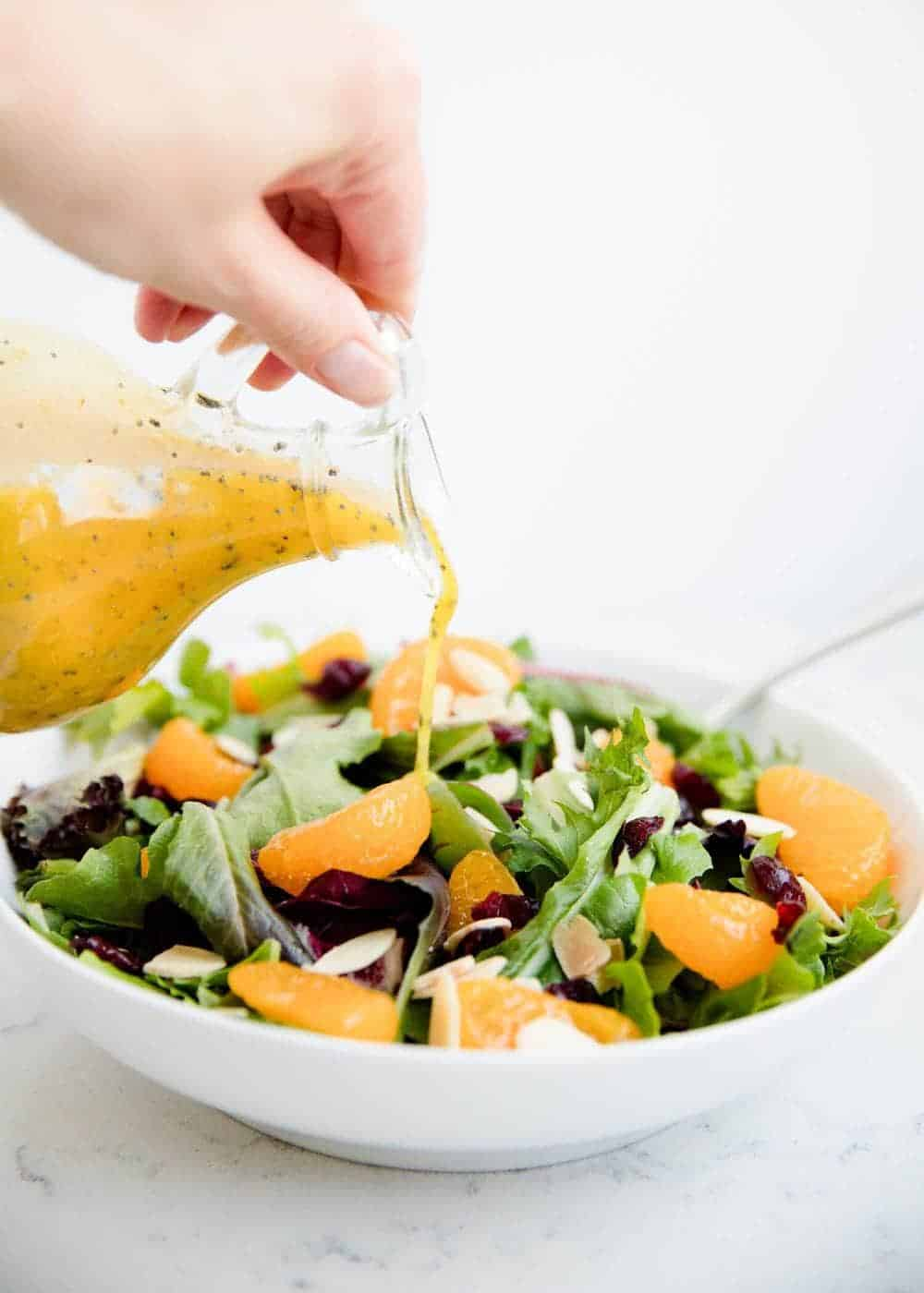 pouring orange vinaigrette over mandarin orange salad