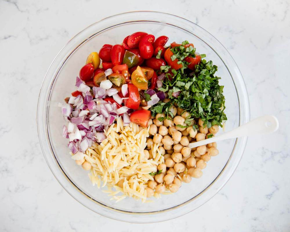 ingredients for orzo salad in a large bowl
