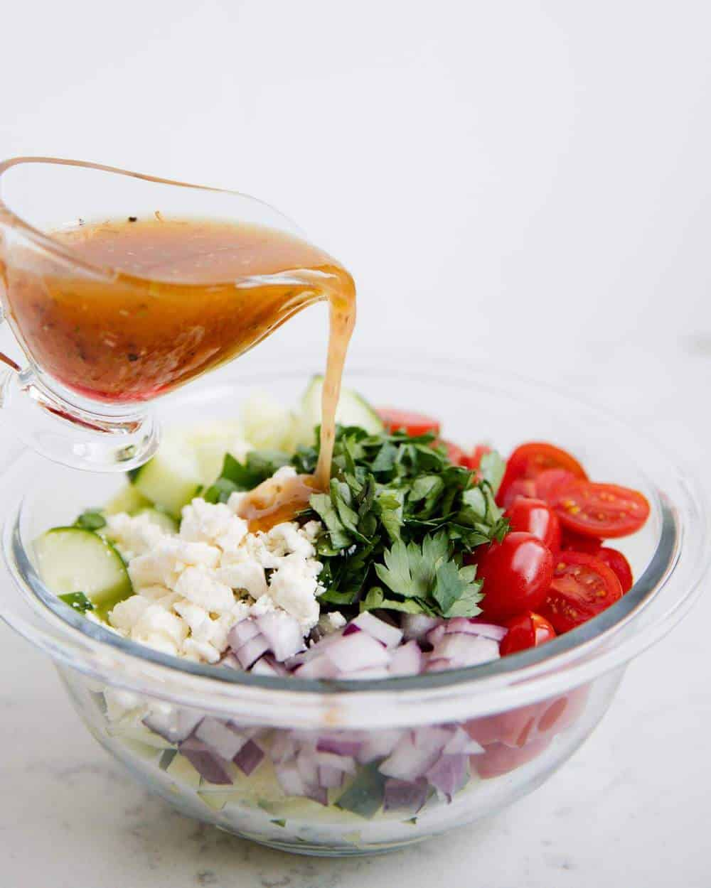 pouring vinaigrette over bowl of ingredients for tomato cucumber salad