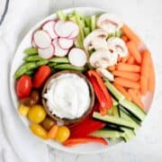bowl of dill dip on a white plate with fresh veggies