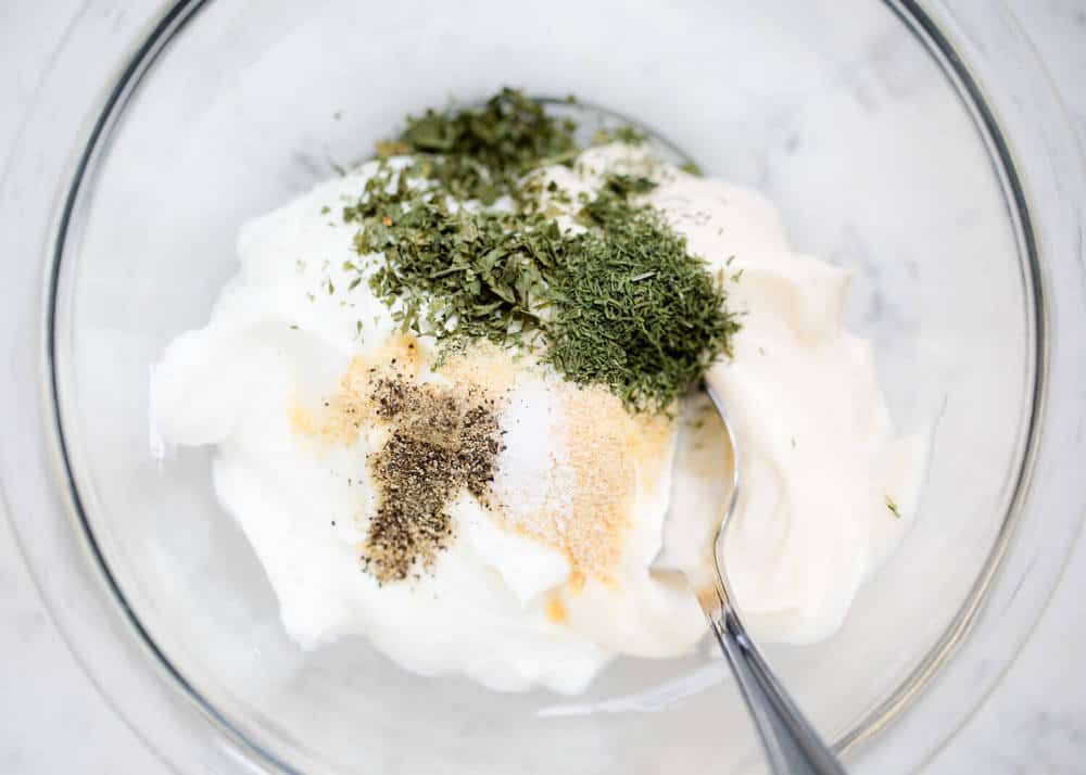 mixing dill dip ingredients in a medium bowl