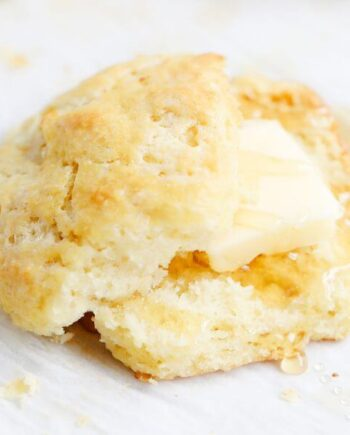 A sliced biscuit with butter and honey