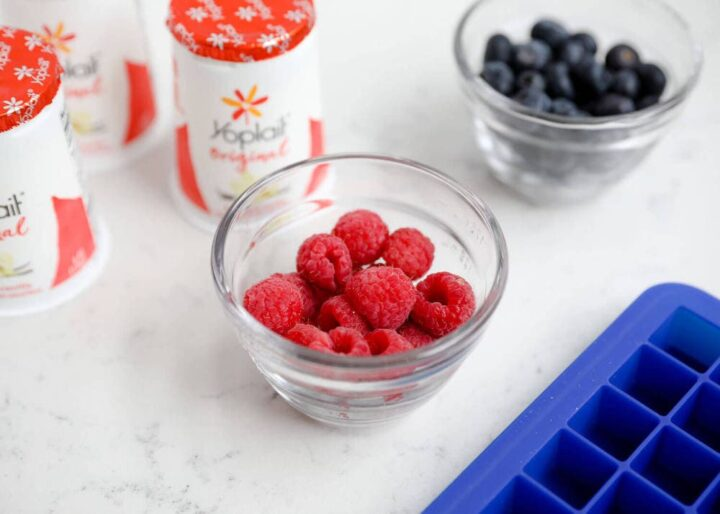 bowls of raspberries and blueberries on the counter with yogurt containers
